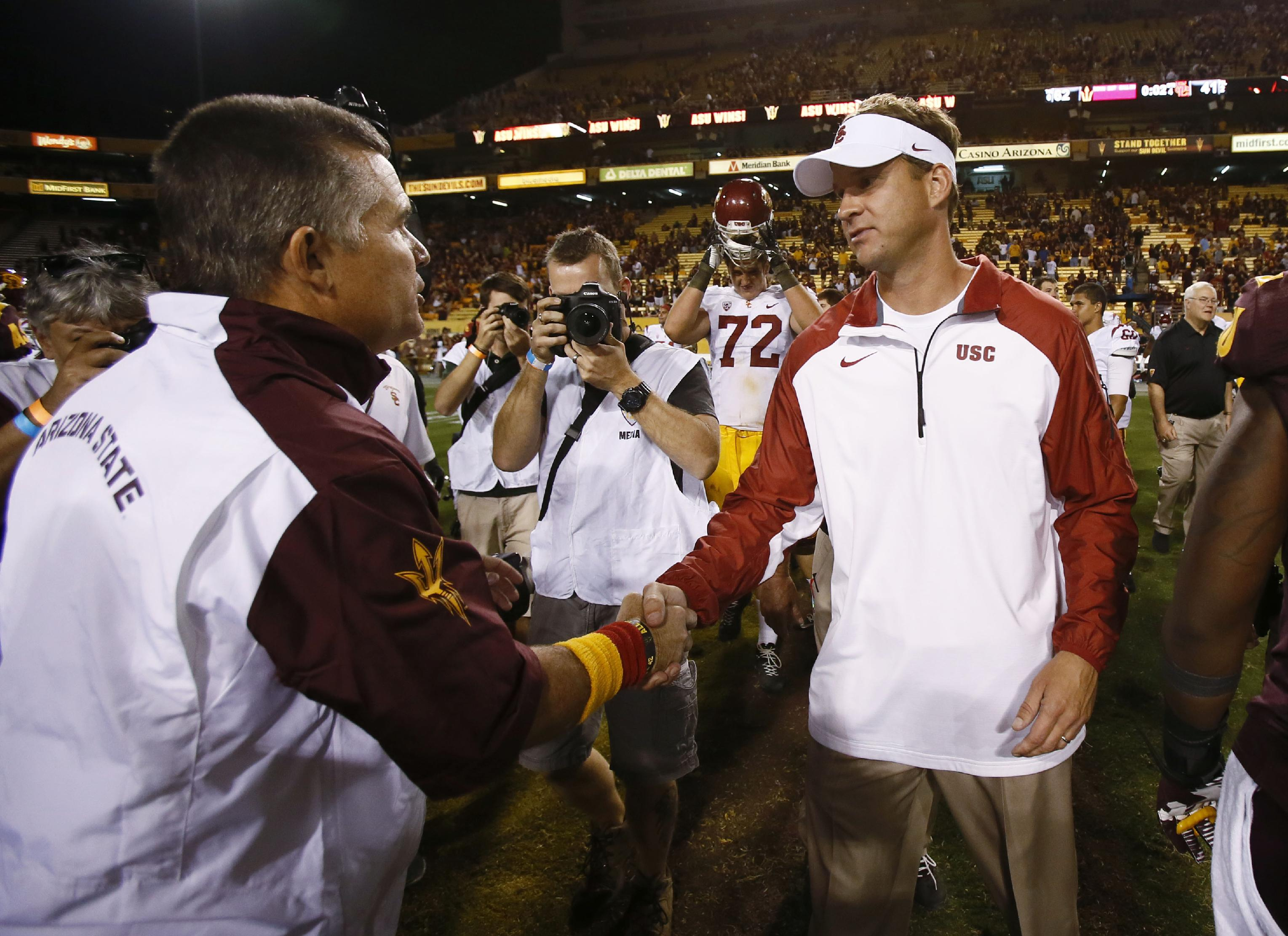 In this Sept. 28, 2013 photo, Arizona State University head coach Todd Graham, left,  shakes hands with USC head coach Lane Kiffin after ASU defeated USC 62-41 at Sun Devil Stadium in Tempe, Ariz. USC fired Kiffin early Sunday morning, not long after the team lost 62-41 at Arizona State