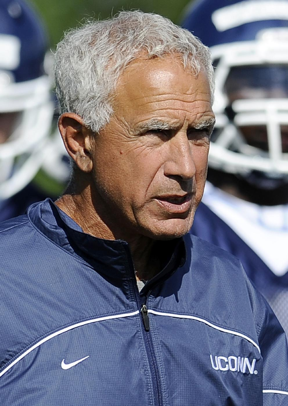 In this Aug. 2, 2013, file photo Connecticut head coach Paul Pasqualoni walks with his team during NCAA college football practice in Storrs, Conn. Paqualoni was fired Monday, Sept. 30, 2013, after the Huskies lost the first four games of the season