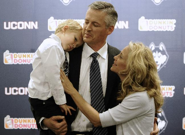 Connecticut interim head coach and former offensive coordinator T.J. Weist, center, holds his son James, left, as his wife Karen, right, watches, after an NCAA college football news conference, Monday, Sept. 30, 2013, in  Storrs, Conn. Weist is taking over for fired coach Paul Pasqualoni