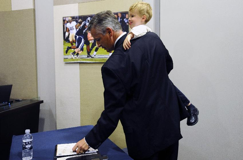 Connecticut interim head coach and former offensive coordinator T.J. Weist leaves an NCAA college football news conference while holding his son James, Monday, Sept. 30, 2013, in Storrs, Conn. Weist is taking over for fired coach Paul Pasqualoni