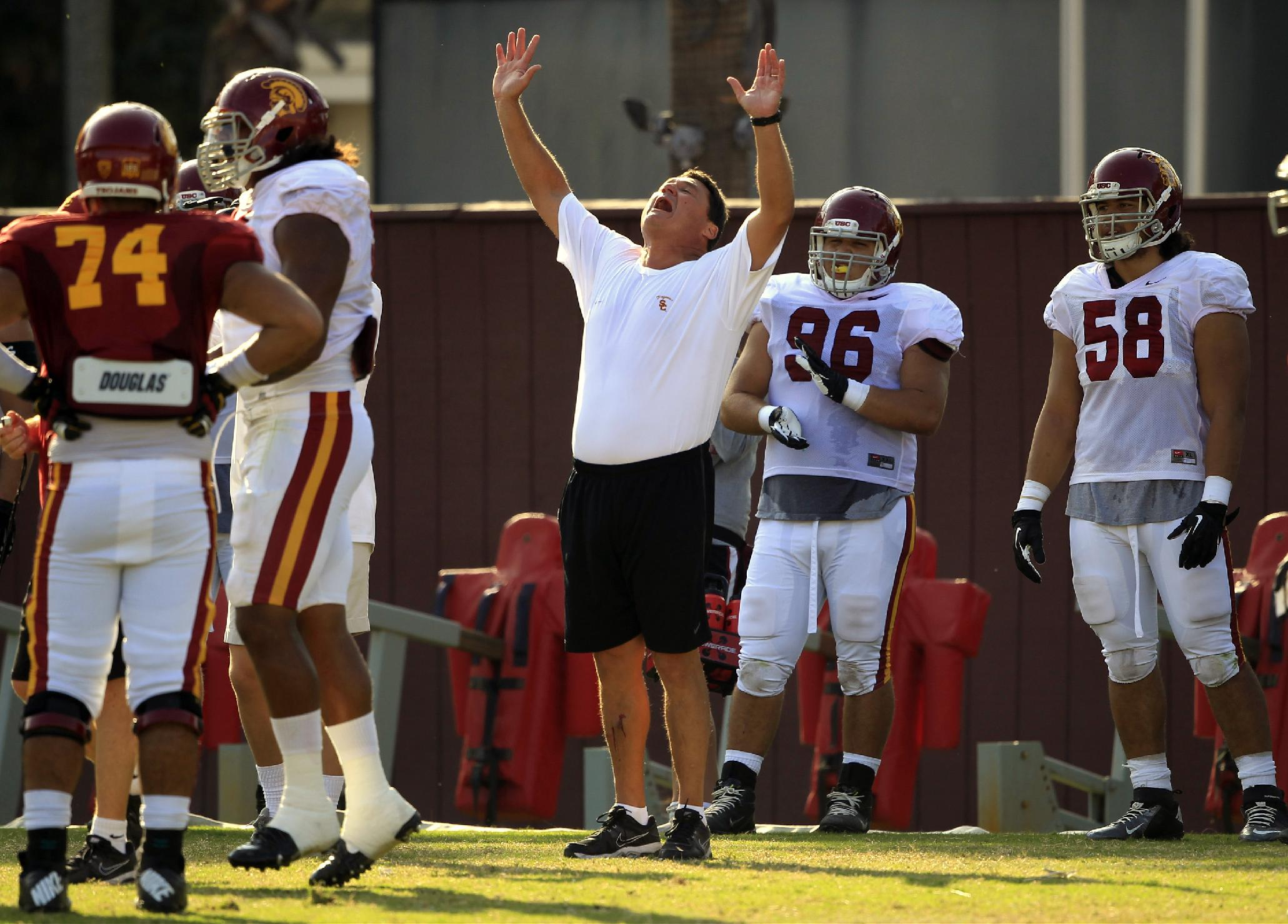 USC Trojans' interim football coach Ed Orgeron, center, lifts his arms during open NCAA college football practice on their Los Angeles campus on Wednesday, Oct. 2, 2013
