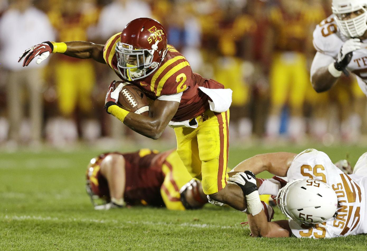 Iowa State running Aaron Wimberly (2) is tripped up by Texas linebacker Dalton Santos (55) during the first half of an NCAA college football game, Thursday, Oct. 3, 2013, in Ames, Iowa