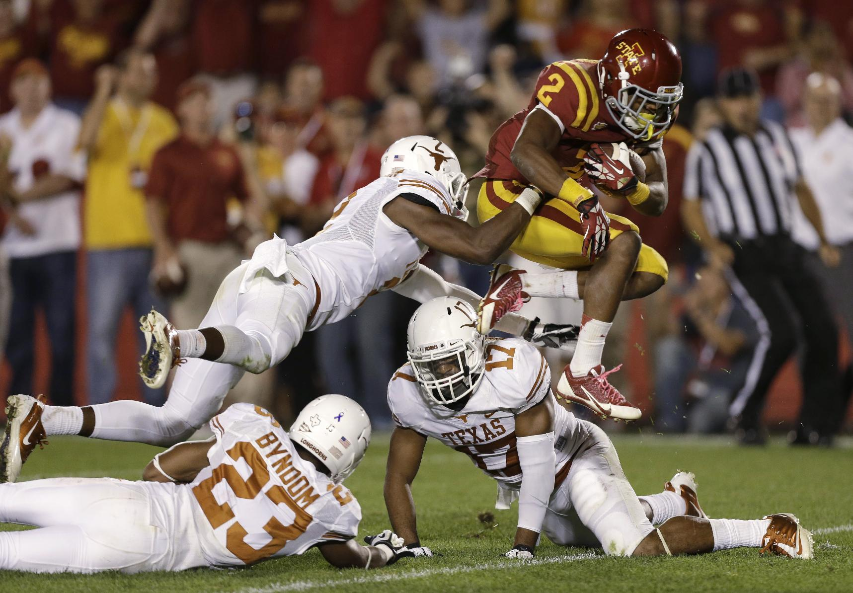 Iowa State running back Aaron Wimberly, right, leaps past Texas defenders Carrington Byndom (23), Mykkele Thompson and Adrian Phillips (17) during a 20-yard touchdown run in the second half of an NCAA college football game, Thursday, Oct. 3, 2013, in Ames, Iowa. Texas won 31-30