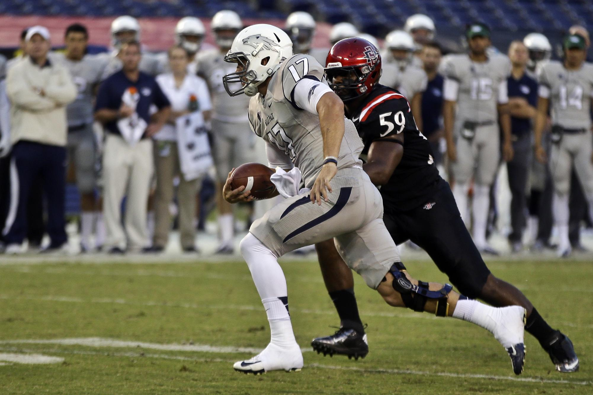 Nevada quarterback Cody Fajardo (17) outruns San Diego State defender Jordan Thomas for a first down during the second quarter of an NCAA college football game on Friday, Oct. 4, 2013, in San Diego