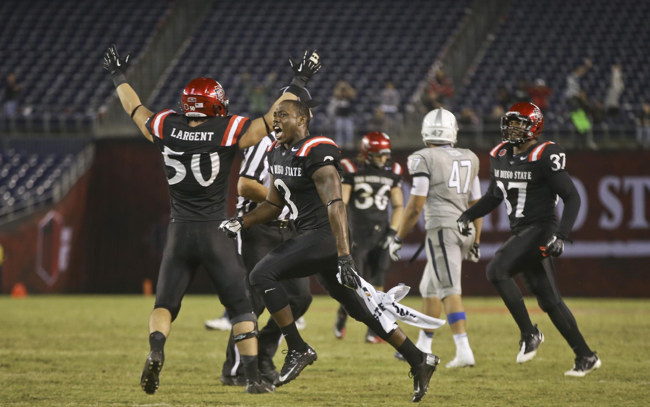 San Diego State's Ezell Ruffin races onto the field as teammates begin their celebration following a 51-44 overtime victory over Nevada in a NCAA college football game  Friday, Oct. 4, 2013, in San Diego