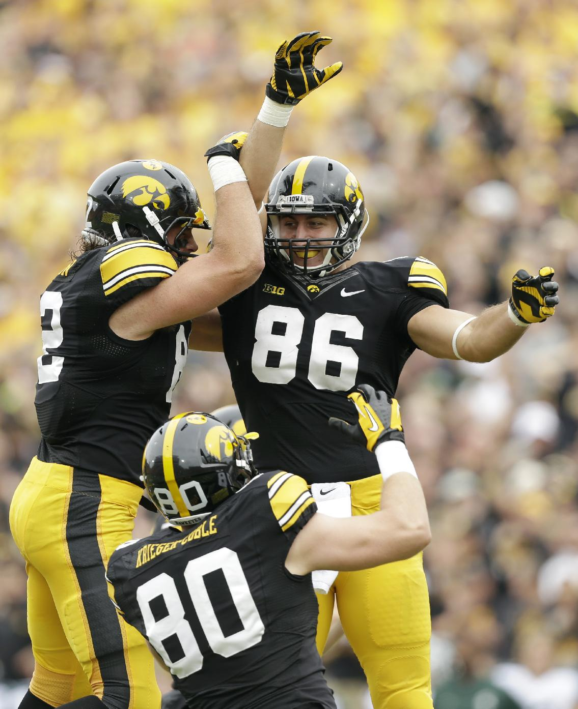 Iowa tight end C.J. Fiedorowicz (86) celebrates with teammates Ray Hamilton, left, and Henry Krieger Coble (80) after catching a 10-yard touchdown pass during the first half of an NCAA college football game against Michigan State, Saturday, Oct. 5, 2013, in Iowa City, Iowa
