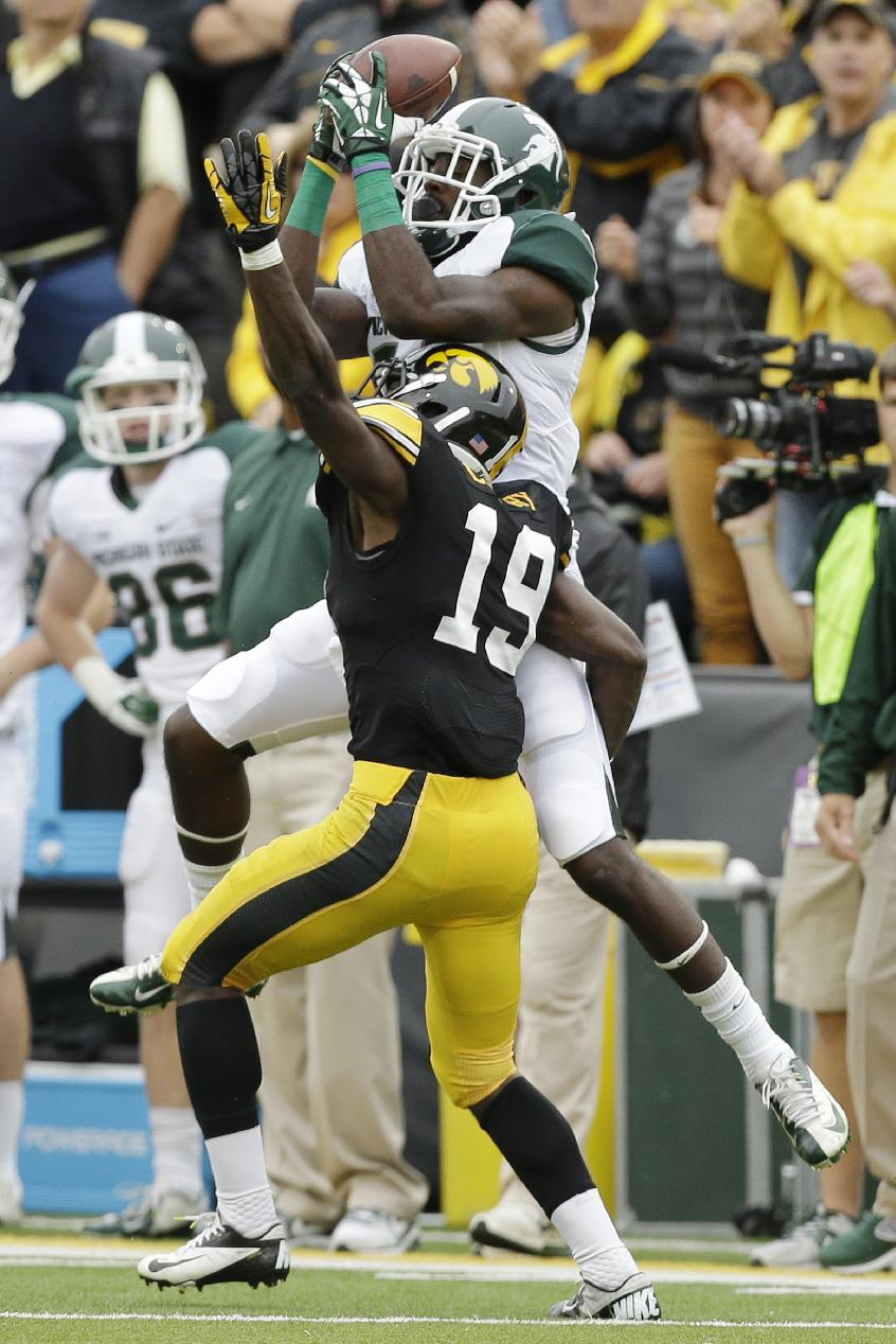 Michigan State wide receiver Tony Lippett, top, catches a pass over Iowa defensive back B.J. Lowery during the first half of an NCAA college football game, Saturday, Oct. 5, 2013, in Iowa City, Iowa