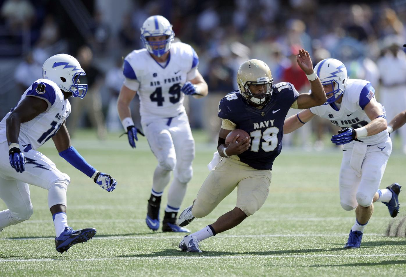 Navy quarterback Keenan Reynolds (19) weaves his way around Air Force defensive back Gavin McHenry, right, Joey Nichol (49) and Reggie Barnes, left, during the second half of an NCAA football game, Saturday, Oct. 5, 2013, in Annapolis, Md. Navy won 28-10