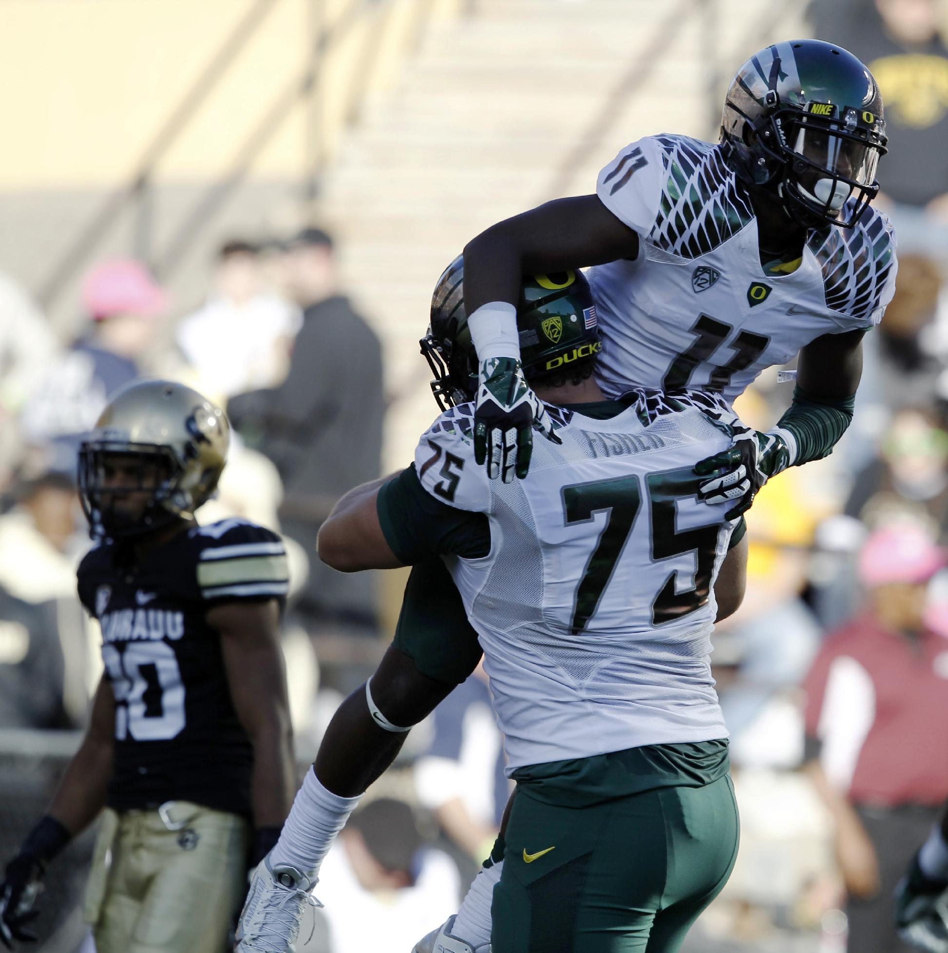 Oregon wide receiver Bralon Addison, front top, is hoisted in the air after his catch for a touchdown by offensive lineman Jake Fisher, front bottom against Colorado during the first quarter of an NCAA college football game in Boulder, Colo., on Saturday, Oct. 5, 2013