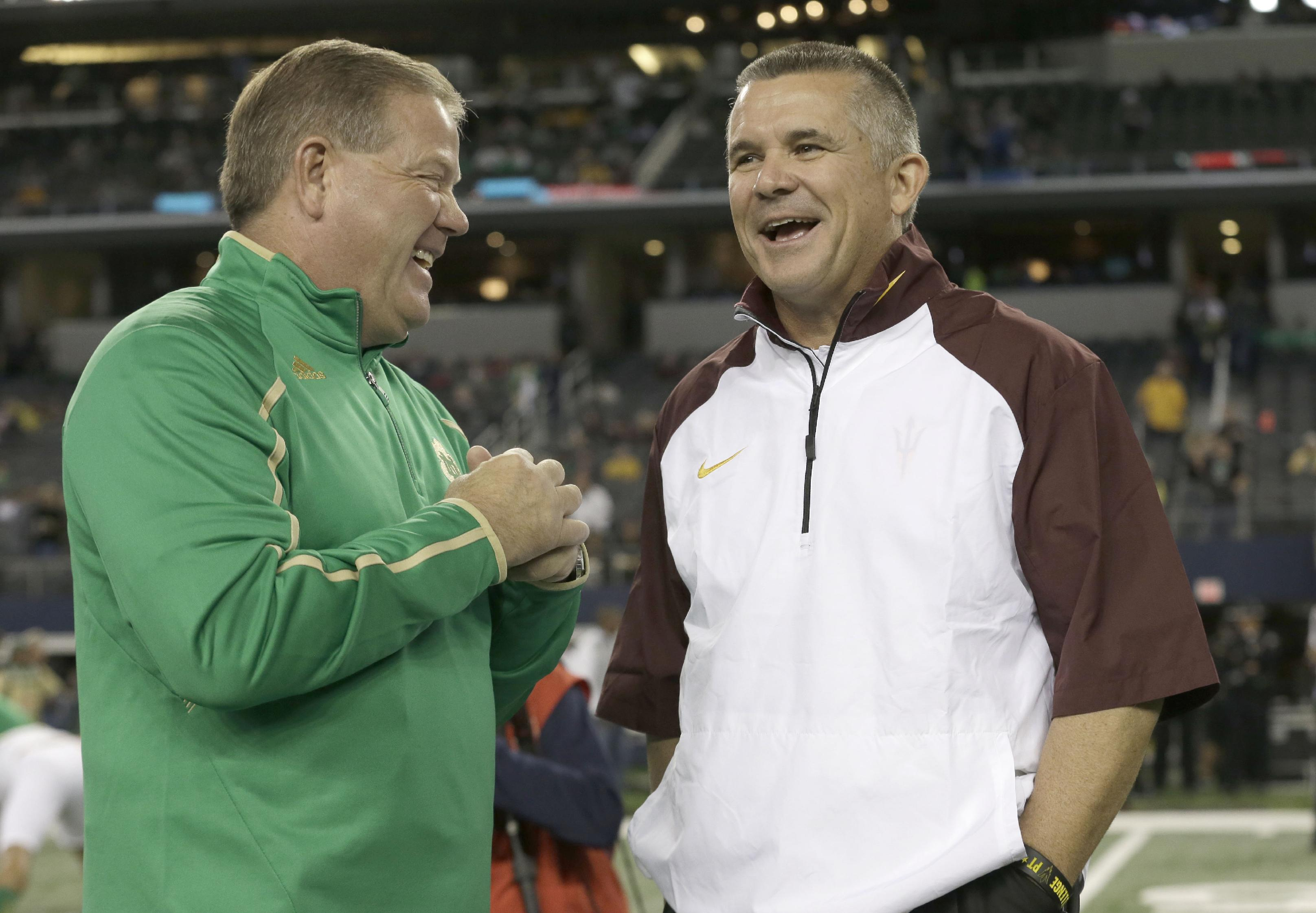 Notre Dame coach Brian Kelly, left, and Arizona State coach Todd Graham chat on the field before an NCAA college football game Saturday, Oct. 5, 2013, in Arlington, Texas