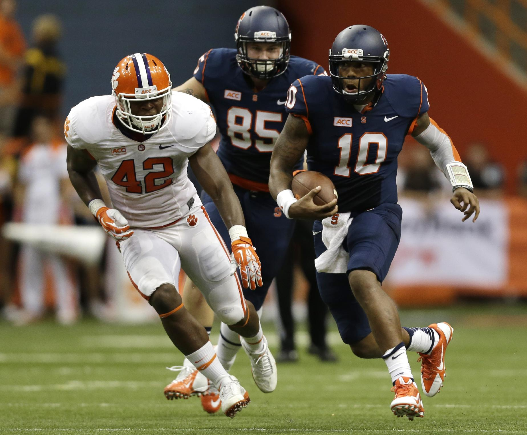 Syracuse quarterback Terrell Hunt (10) runs from Clemson linebacker Stephone Anthony (42) during the second half of an NCAA college football game on Saturday, Oct. 5, 2013, in Syracuse, N.Y. Clemson won, 49-14
