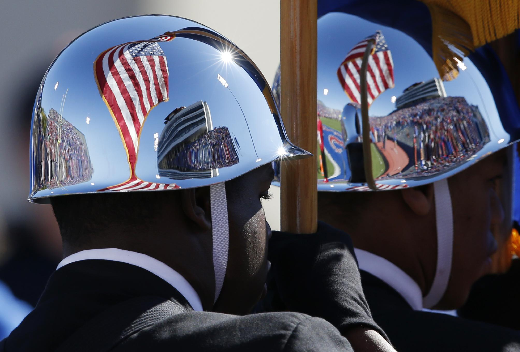 The flag is reflected in the helmet of a Junior ROTC color guard member before an NCAA college football game between Oklahoma and Kansas in Lawrence, Kan., Saturday, Oct. 19, 2013