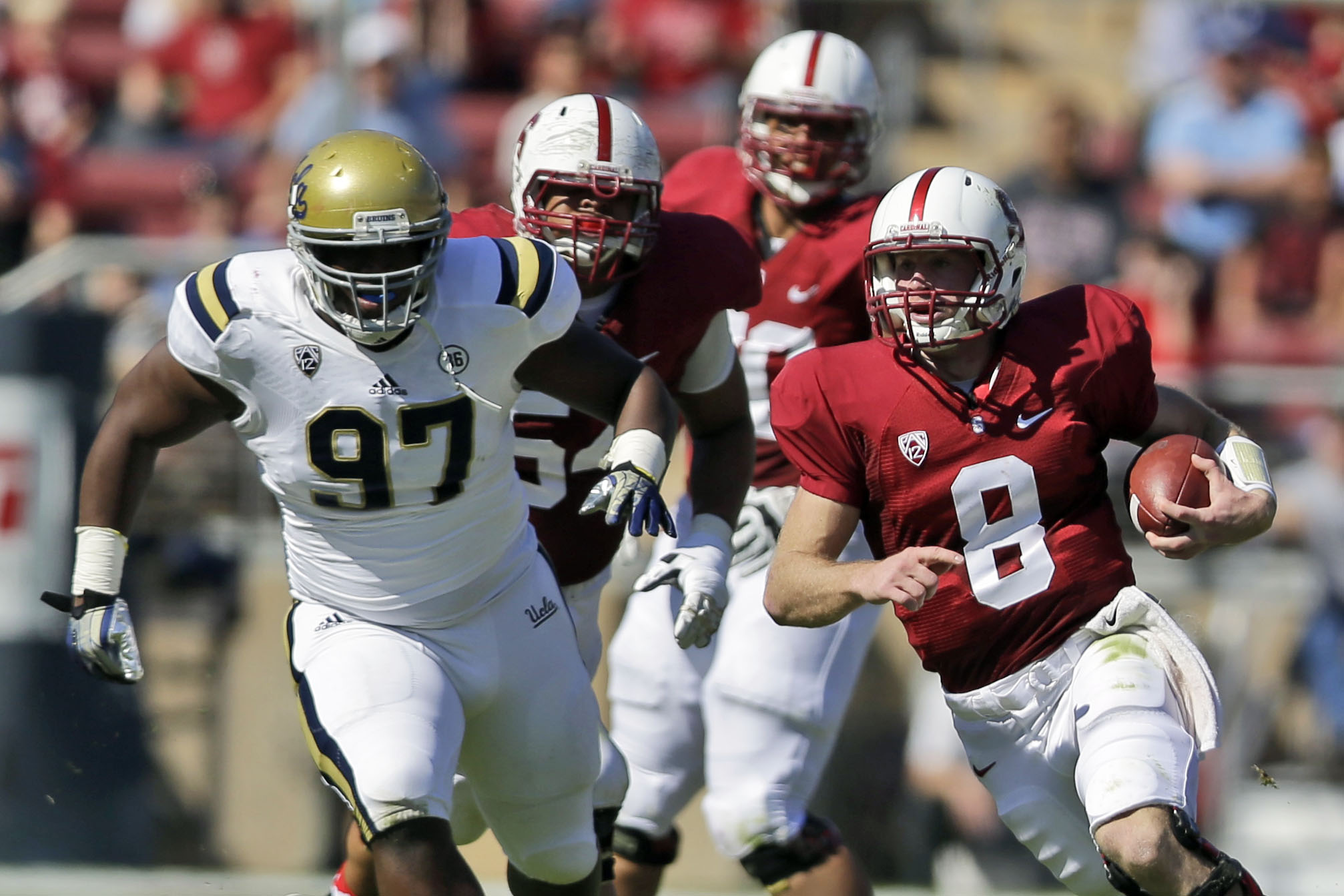 Stanford quarterback Kevin Hogan (8) is chased by UCLA defensive tackle Kenneth Clark (97) during the first half of an NCAA college football game on Saturday, Oct. 19, 2013, in Stanford, Calif