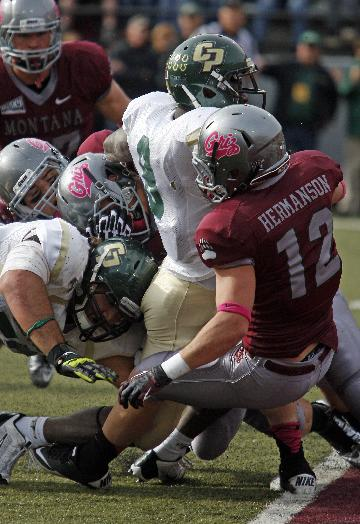 Cal Poly fullback Akaninyene Umoh (8) scores in the first quarter against Montana as free safety Matt Hermanson (12) tries to stop him during an NCAA college football game in Missoula, Mont., Saturday, Oct. 19, 2013