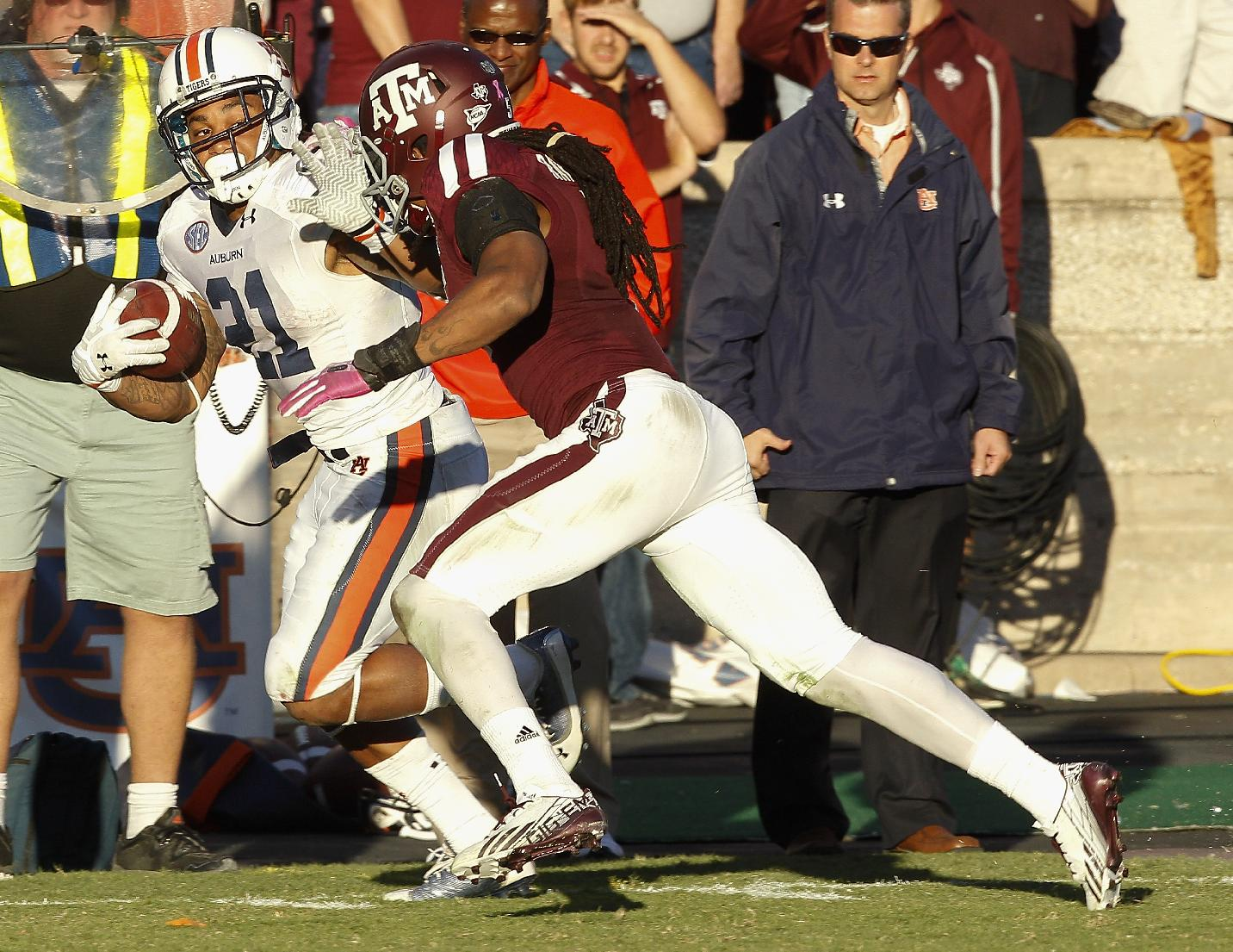 Auburn running back Tre Mason (21) fends off Texas A&M defensive back Floyd Raven Sr. (5)  for a 53-yard run in the fourth quarter of an NCAA college football game Saturday, Oct. 19, 2013, in College Station, Texas. Auburn won 45-41