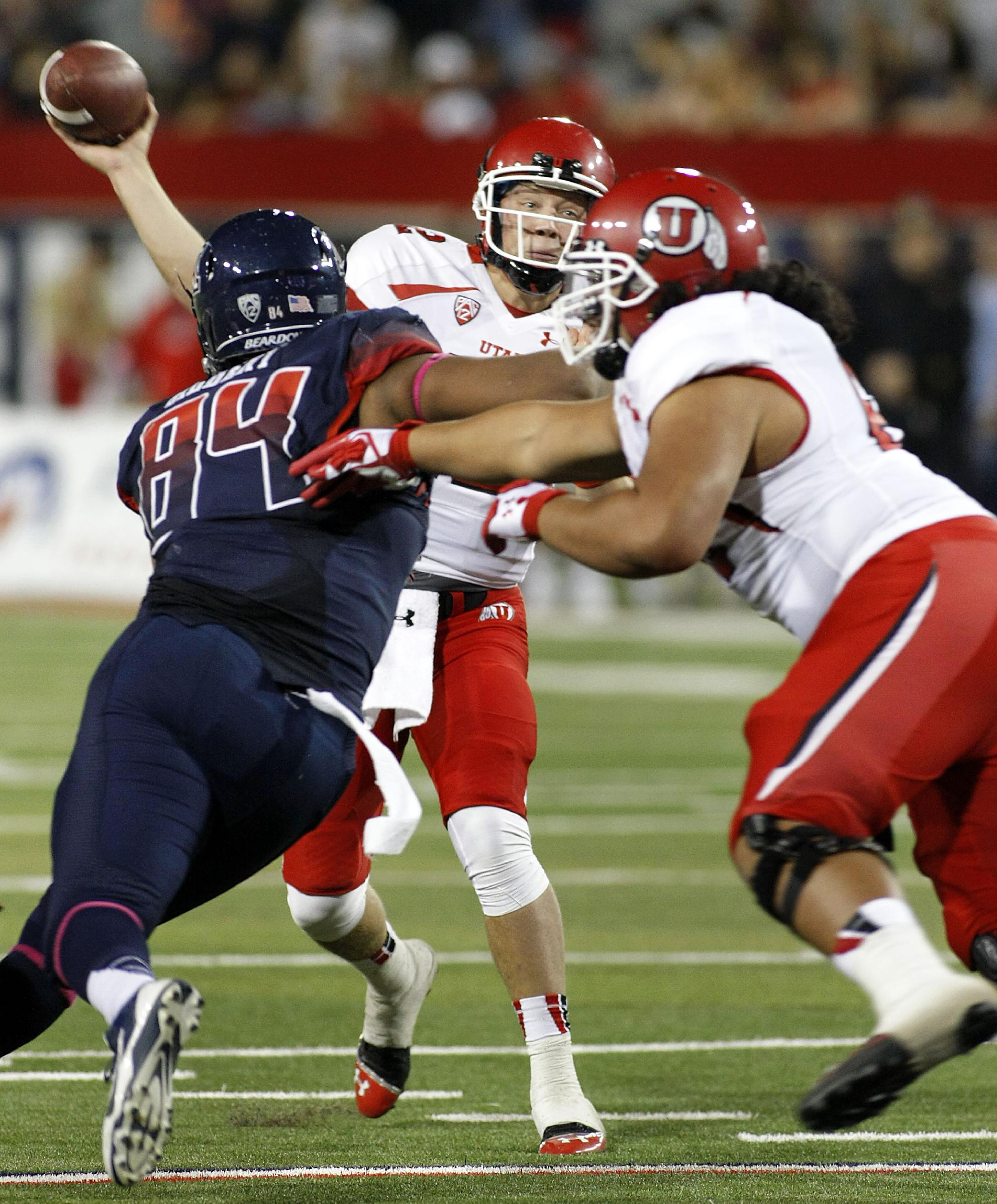 Utah's quarterback Adam Schulz (in back) throws over the Arizona rush in the second half of an NCAA collge football game, Saturday, Oct. 19, 2013 in Tucson, Ariz. Arizona won 35 to 24