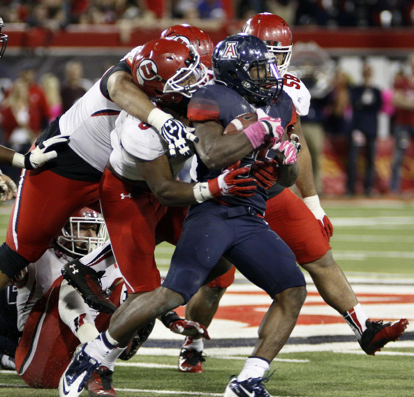 Arizona's Ka'Deem Carey (25) is gang tackled by Utah's Nate Orchard (8), Tenny Palepoi, left, and Junior Salt (59) in the second half of an NCAA college football game, Saturday, Oct. 19, 2013 in Tucson, Ariz.  Arizona won 35 - 24