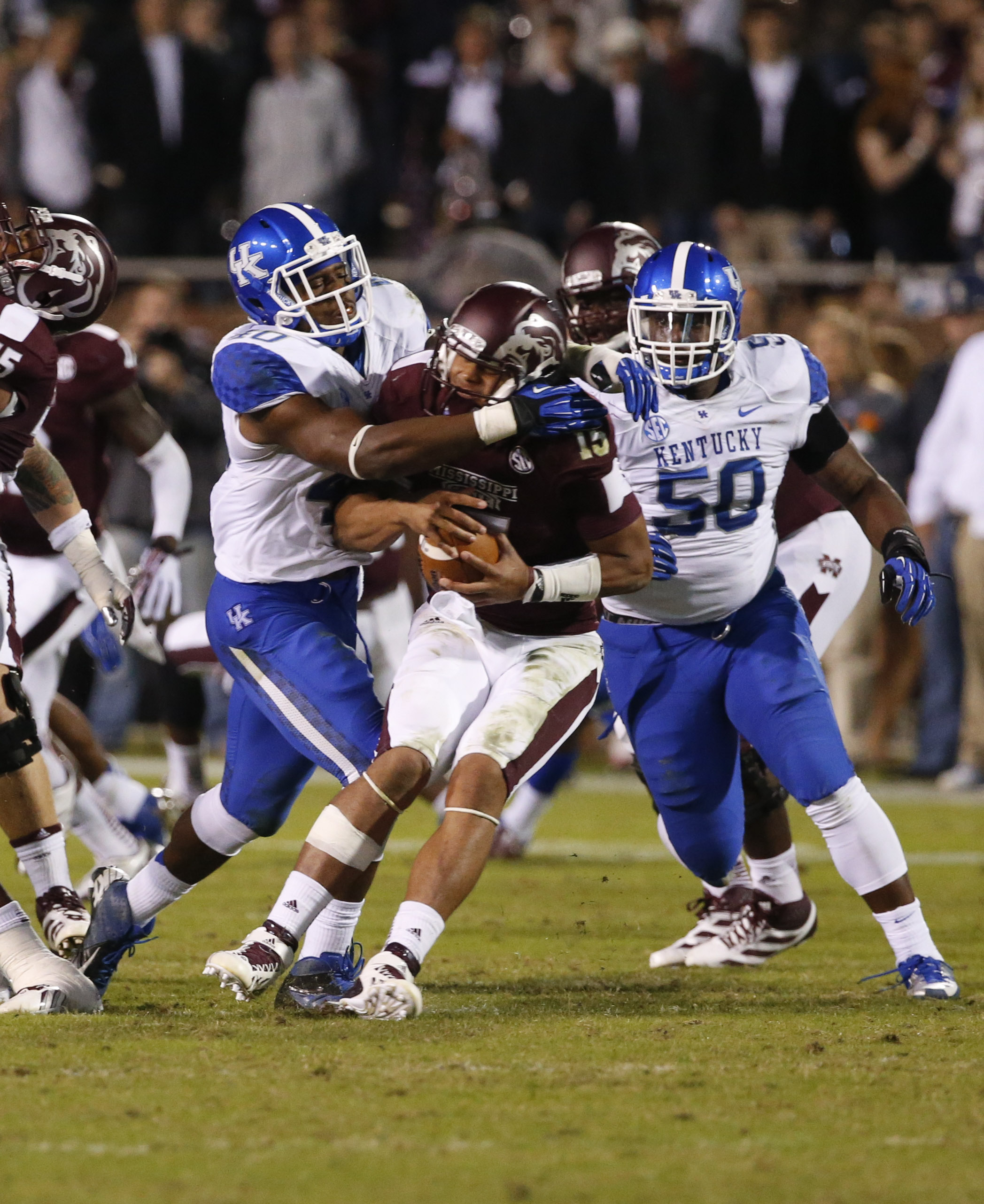 Mississippi State quarterback Dak Prescott (15) is sacked by Kentucky linebacker Avery Williamson, left, and defensive lineman Mike Douglas (50) in the second half of their NCAA college football game at Davis Wade Stadium in Starkville, Miss., Thursday, Oct. 24, 2013. Mississippi State won 28-22