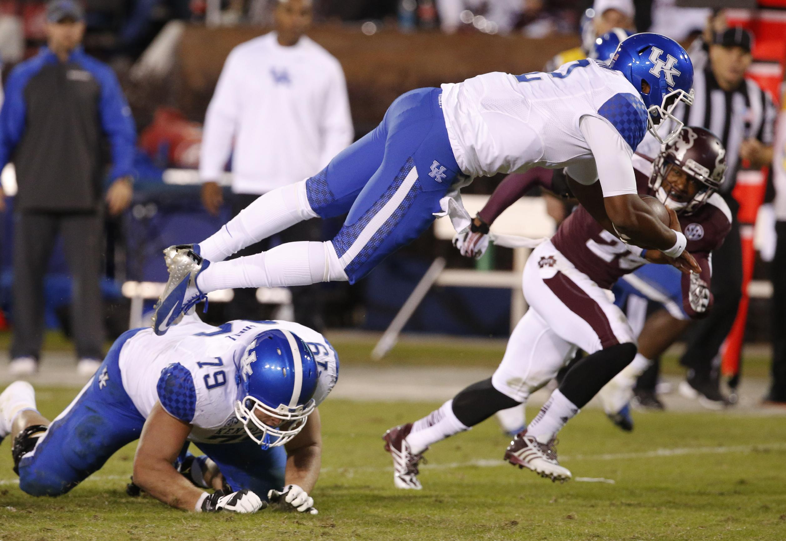 Kentucky quarterback Jalen Whitlow (2) dives over his guard Kevin Mitchell (79) for short yardage in the second half of their NCAA college football game against Mississippi State at Davis Wade Stadium in Starkville, Miss., Thursday, Oct. 24, 2013. Mississippi State won 28-22