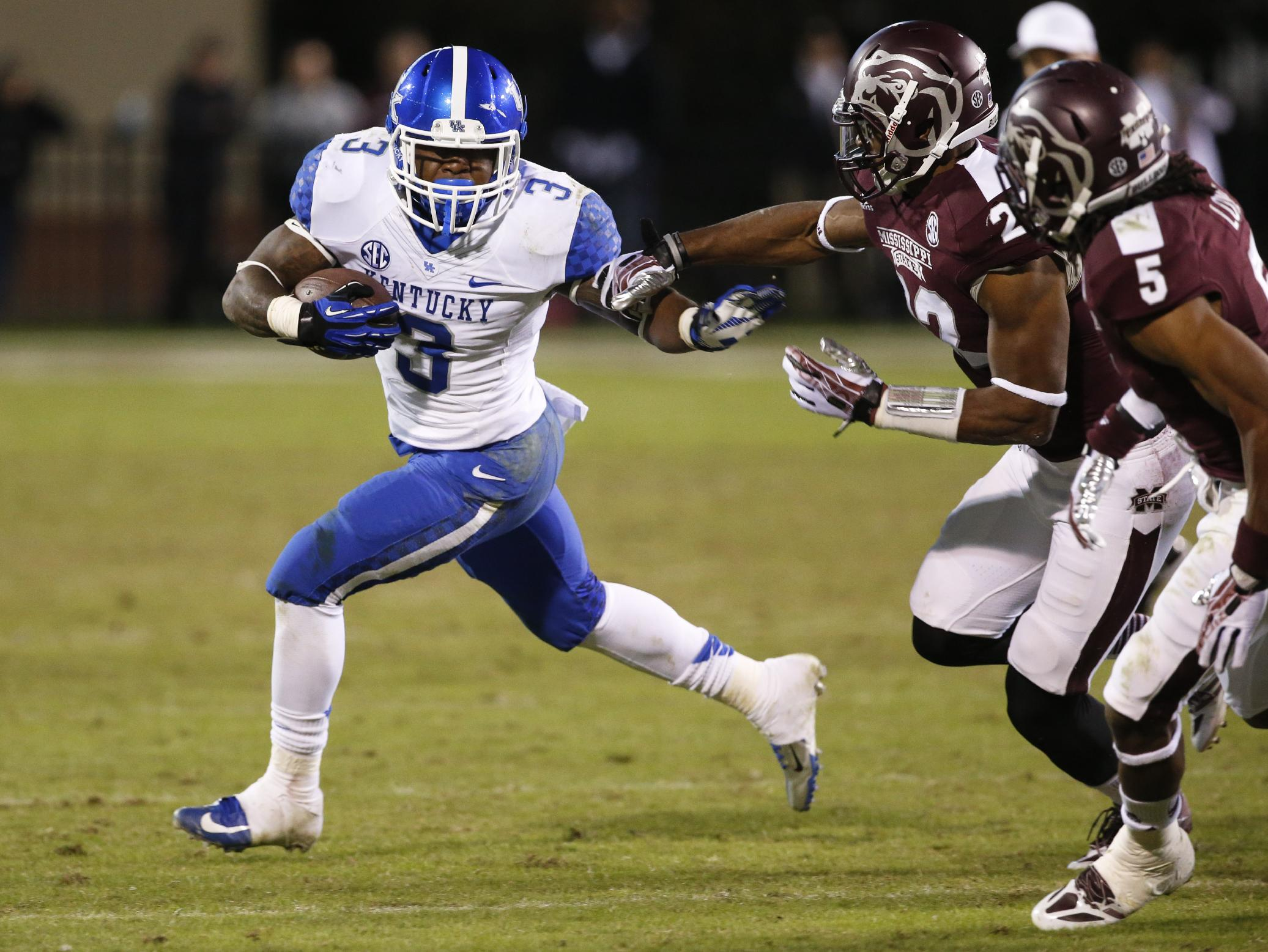Kentucky running back Jojo Kemp (3) attempts to outrun Mississippi State linebacker Matthew Wells (22) and  defensive back Jamerson Love (5) in the second half of their NCAA college football game at Davis Wade Stadium in Starkville, Miss., Thursday, Oct. 24, 2013. Mississippi State won 28-22
