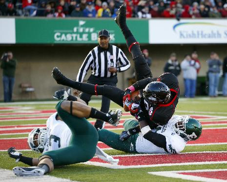 Northern Illinois linebacker Bobby Jones IV, center, rolls over Eastern Michigan defensive back Willie Creear, right, as teammate Donald Coleman, left, rolls away during the second half of an NCAA college football game on Saturday, Oct. 26, 2013, in DeKalb, Ill