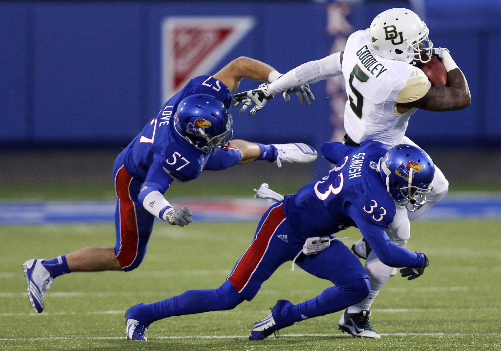 Baylor Bears wide receiver Antwan Goodley catches a pass against Kansas Jayhawks linebacker Jake Love (57) and Cassius Sendish (33) in the first quarter of an NCAA college football game Saturday, Oct. 26, 2013, in Lawrence, Kan