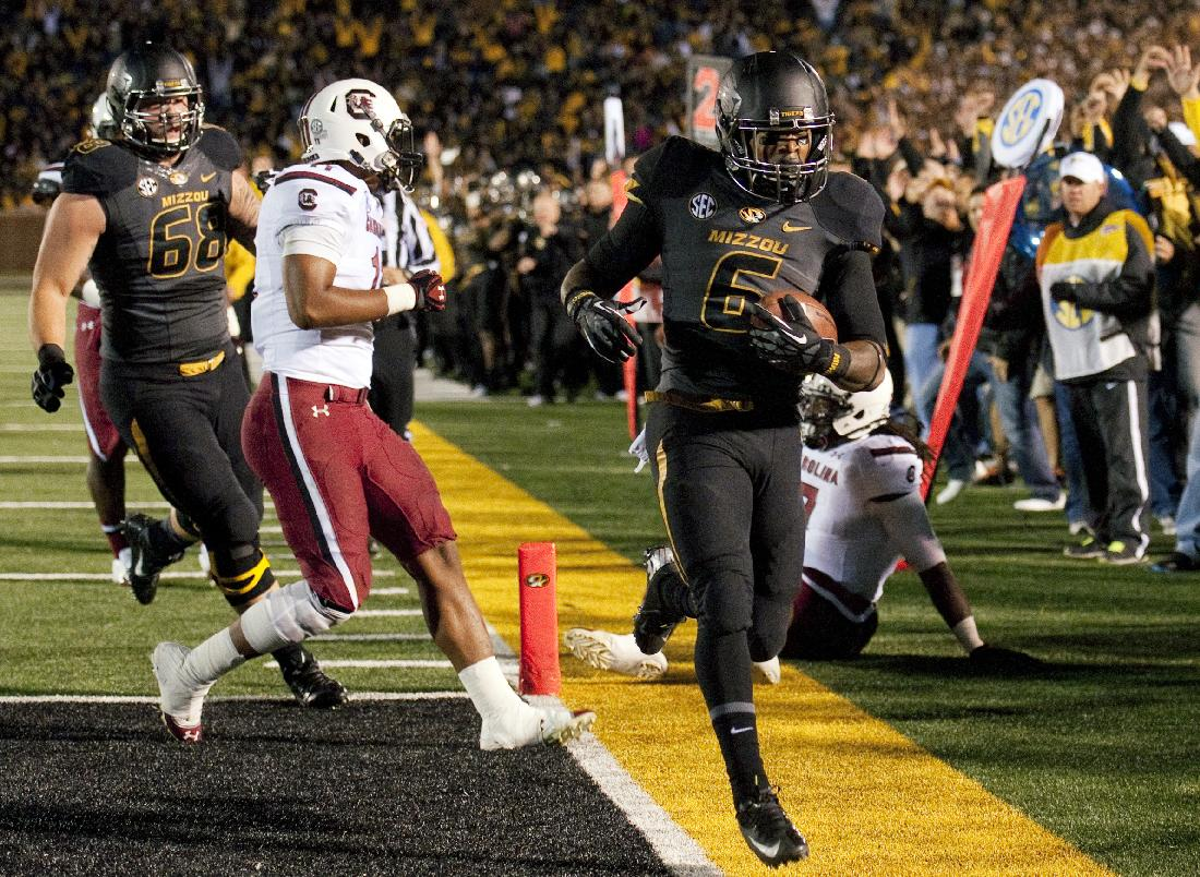 Missouri's Marcus Murphy, right, scores a touchdown in front of South Carolina's T.J. Holloman, center, and Missouri's Justin Britt (68) during the first quarter of an NCAA college football game Saturday, Oct. 26, 2013, in Columbia, Mo