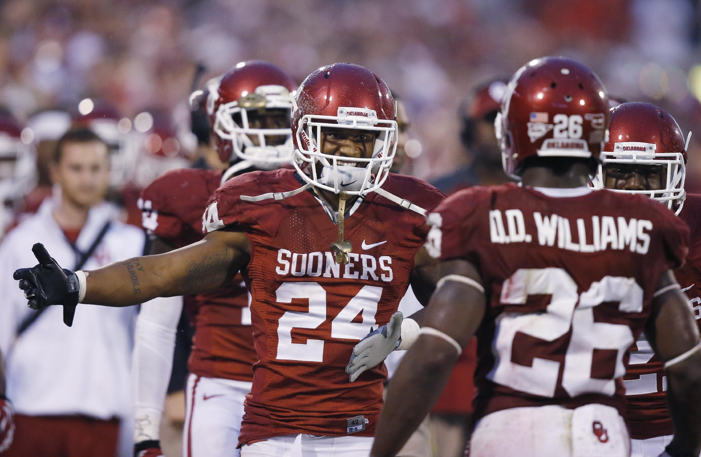 Oklahoma running back Brennan Clay (24) greets teammate Damien Williams (26) on the sidelines after Williams scored a touchdown against Texas Tech in the fourth quarter of an NCAA college football game in Norman, Okla., Saturday, Oct. 26, 2013. Oklahoma won 38-30