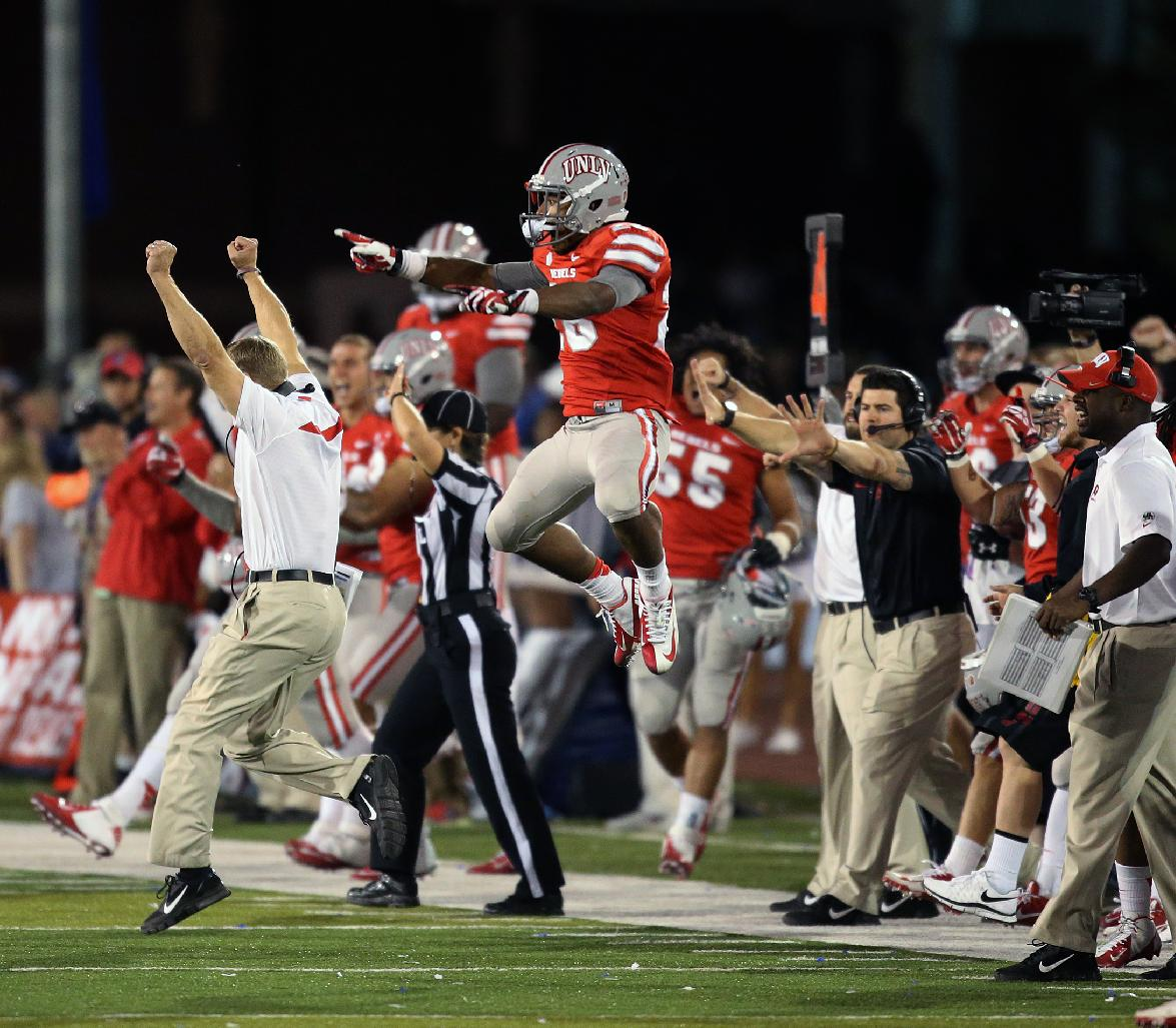 The UNLV sideline celebrates their victory against Nevada in the final seconds during the second half of an NCAA college football game in Reno, Nev., on Saturday, Oct. 26, 2013. UNLV defeated Nevada 27-22