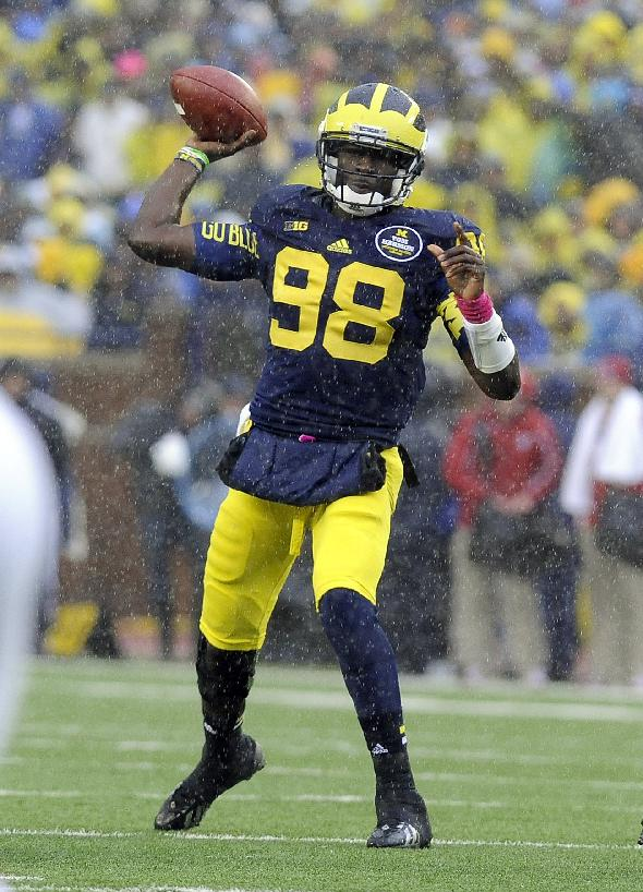 In this Oct. 19, 2013 file photo, Michigan quarterback Devin Gardner throws a pass in the rain during an NCAA college football game against Indiana in Ann Arbor, Mich. Heading into the final month of regular season Michigan is battling for supremacy in the  Big Ten's Legends Division with Michigan  State and Nebraska