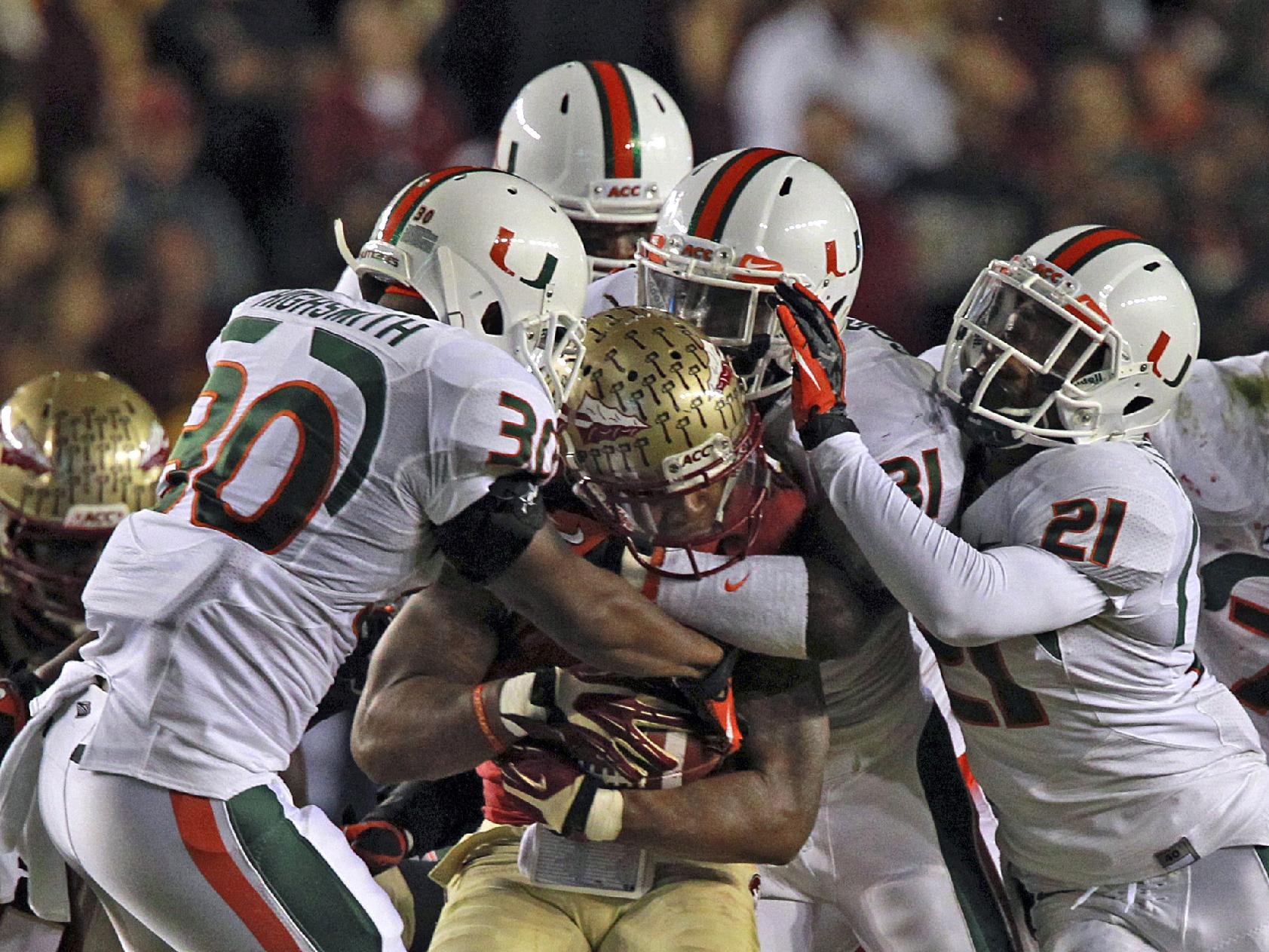 Miami's defense smoothers Florida State's Karlos Williams in the first quarter of an NCAA college football game Saturday, Nov. 2, 2013, in Tallahassee, Fla