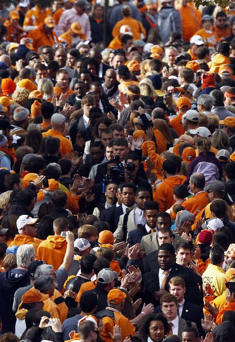 Tennessee player's make their way through fans during the Vol Walk before an NCAA college football game against Auburn on Saturday, Nov. 9, 2013 in Knoxville, Tenn