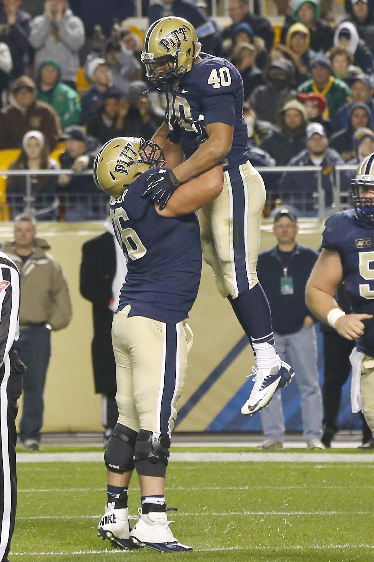 Pittsburgh running back James Conner (40) is lifted into the air by offensive linesman Ryan Schlieper (76) after scoring a touchdown in the third quarter of an NCAA college football game against Notre Dame on Saturday, Nov. 9, 2013, in Pittsburgh. Pittsburgh won 28-21