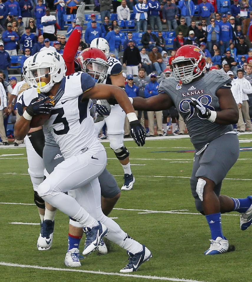 West Virginia running back Charles Sims (3) breaks past Kansas linebacker Ben Heeney, rear, and defensive lineman Keon Stowers (98) for a touchdown during the first half of an NCAA college football game at Kansas Memorial Stadium in Lawrence, Kan., Saturday, Nov. 16, 2013