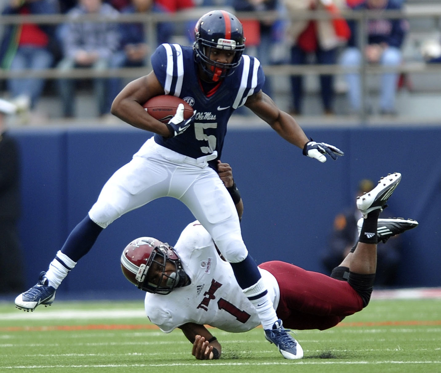 Mississippi running back I'Tavius Mathers (5) is tackled by Troy safety Camren Hudson (1) during an NCAA college football game in Oxford, Miss., Saturday, Nov. 16, 2013. Troy recovered the ball