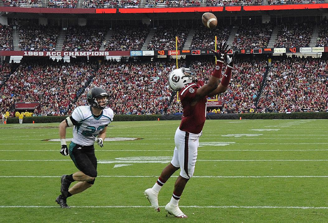 South Carolina wide receiver Pharoh Cooper (11) catches a touchdown pass as Coastal Carolina defensive back Richie Sampson (23) defends during the first half of an NCAA college football game, Saturday, Nov. 23, 2013, in Columbia, S.C
