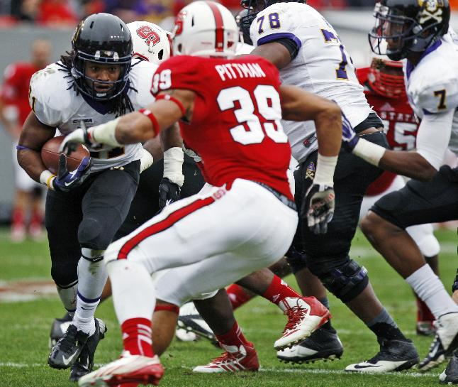 Eastern Carolina's Vintavious Cooper (21) tries to get past North Carolina State defenders during an NCAA college football game in Raleigh, N.C., Saturday, Nov. 23, 2013