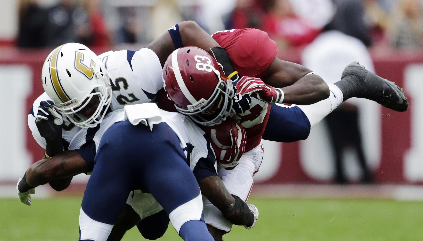 Chattanooga linebacker Wes Dothard (25) and defensive back Chaz Moore, bottom, stop Alabama wide receiver Kevin Norwood (83) during the first half of an NCAA college football game in Tuscaloosa, Ala., Saturday, Nov. 23, 2013