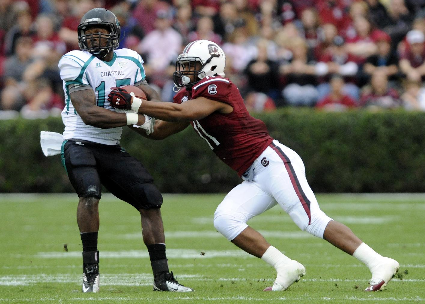 Coastal Carolina running back Lorenzo Taliaferro (15) catches a pass as South Carolina linebacker T.J. Holloman (11) defends during the first half of an NCAA college football game, Saturday, Nov. 23, 2013, in Columbia, S.C