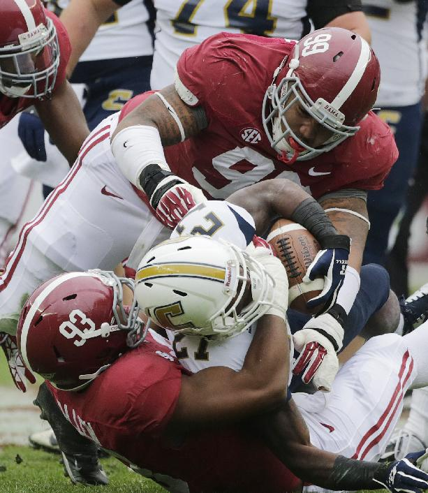 Chattanooga running back Kendrix Huitt (27) is taken down by Alabama defensive lineman Brandon Ivory (99) and linebacker Jonathan Allen (93) during the first half of an NCAA college football game in Tuscaloosa, Ala., Saturday, Nov. 23, 2013