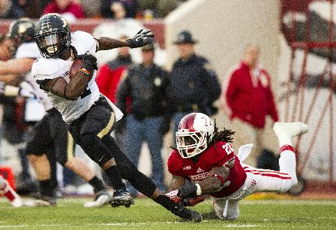 Purdue's Akeem Hunt, left, slips away from Indiana's Kenny Mullen (22) after fielding a kickoff during the first half of an NCAA college football game Saturday, Nov. 30, 2013, in Bloomington, Ind