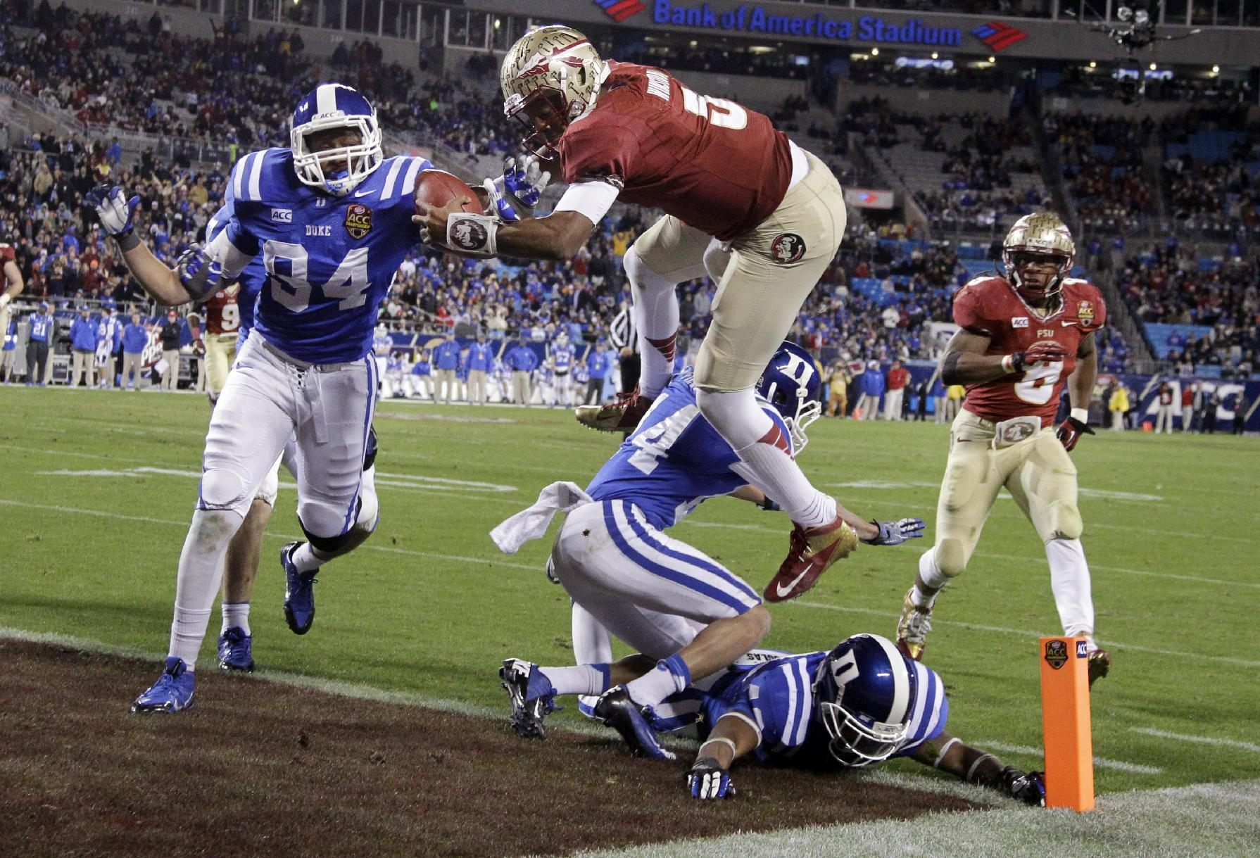 Florida State's Jameis Winston, top center, leaps over Duke's Bryon Fields (14) for a touchdown in the second half of the Atlantic Coast Conference Championship NCAA football game in Charlotte, N.C., Saturday, Dec. 7, 2013. Florida State won 45-7
