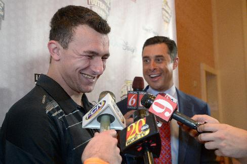 Texas A&M quarterback Johnny Manziel, left, answers questions during a media availability prior to the College Football Awards show in Lake Buena Vista, Fla., Wednesday, Dec. 11, 2013