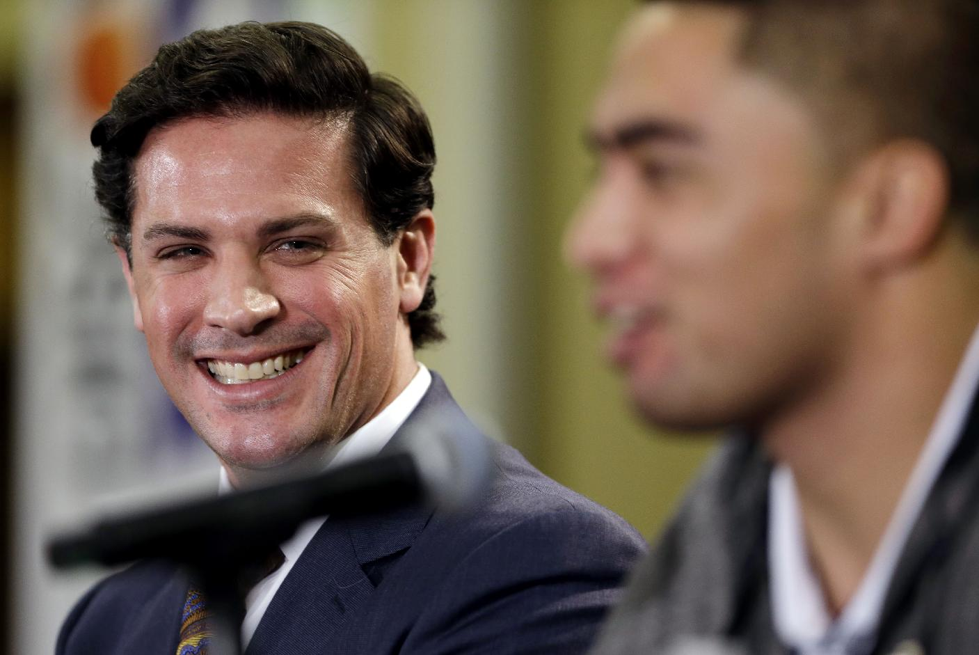 In this Jan. 3, 2013 photo, Notre Dame defensive coordinator Bob Diaco, left, smiles as he and linebacker Manti Te'o speak during a news conference in Fort Lauderdale, Fla. Connecticut has hired Notre Dame defensive coordinator Bob Diaco as its football coach. The school announced the move early Thursday morning, Dec. 12, 2013