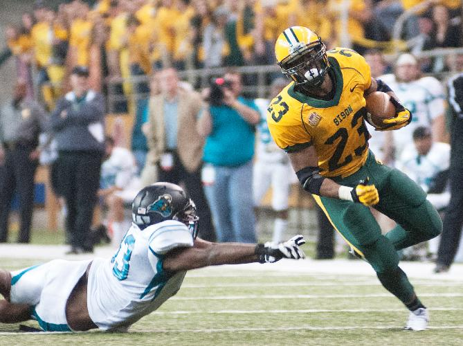 North Dakota State running back John Crockett (23) eludes Coastal Carolina defender Dominique Whiteside during an NCAA college football game in the quarterfinals of the Football Championship Subdivision playoffs Saturday, Dec. 14, 2013, in Fargo, N.D