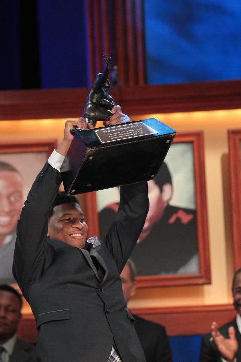 In this photo provided by the Heisman Trust, Florida State quarterback Jameis Winston hoists the Heisman Trophy after being named college football's best player during the Heisman Trophy presentation in New York on Saturday, Dec. 14, 2013. Winston, 19, is the youngest winner of the trophy and the second straight player to win the prestigious award in his first year of college