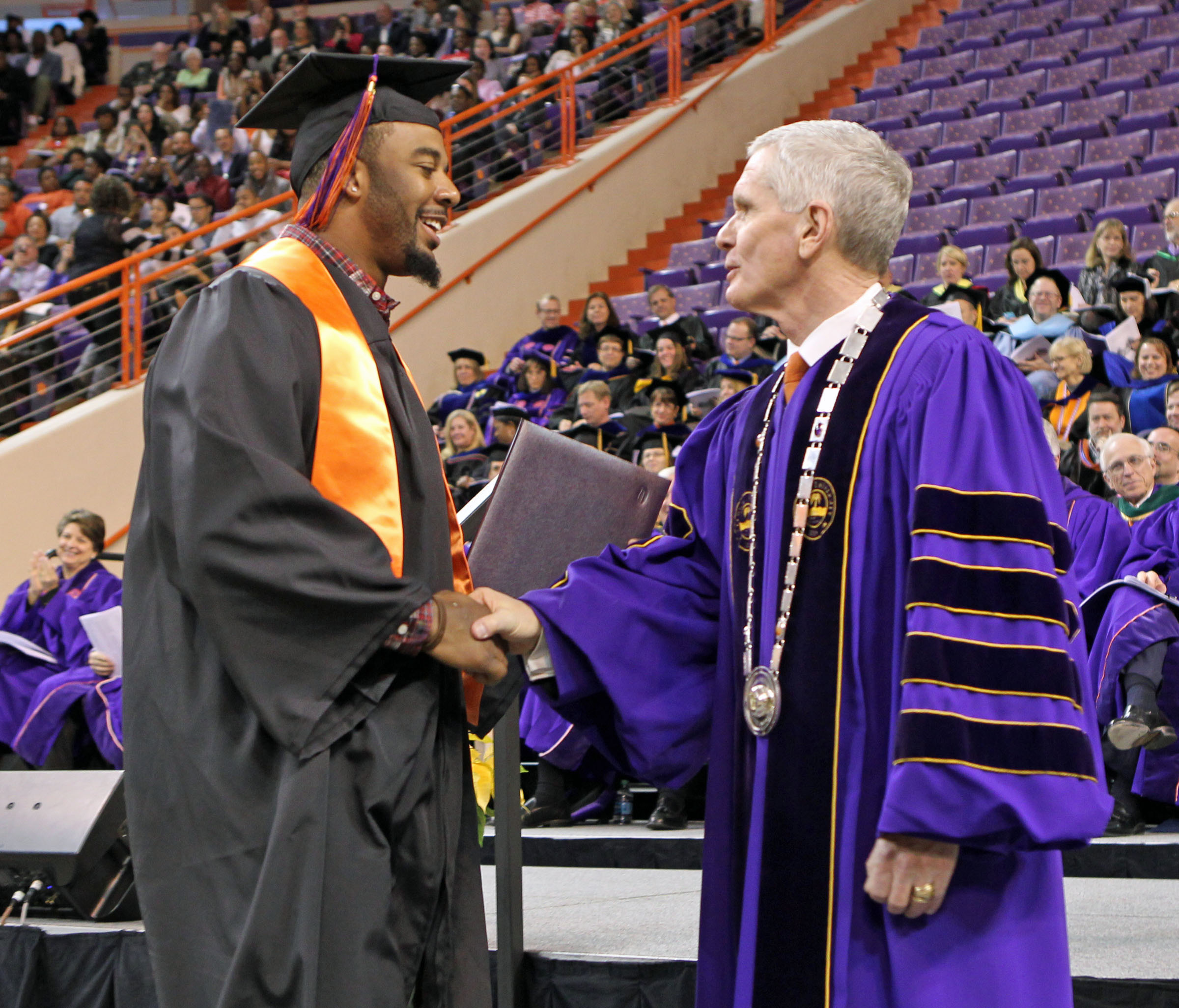 Clemson NCAA college football quarterback Tajh Boyd, left, shakes hands with Clemson University President James F. Barker after receiving his degree in sociology during commencement ceremonies at Littlejohn Coliseum in Clemson, S.C. on Thursday, Dec. 19, 2013