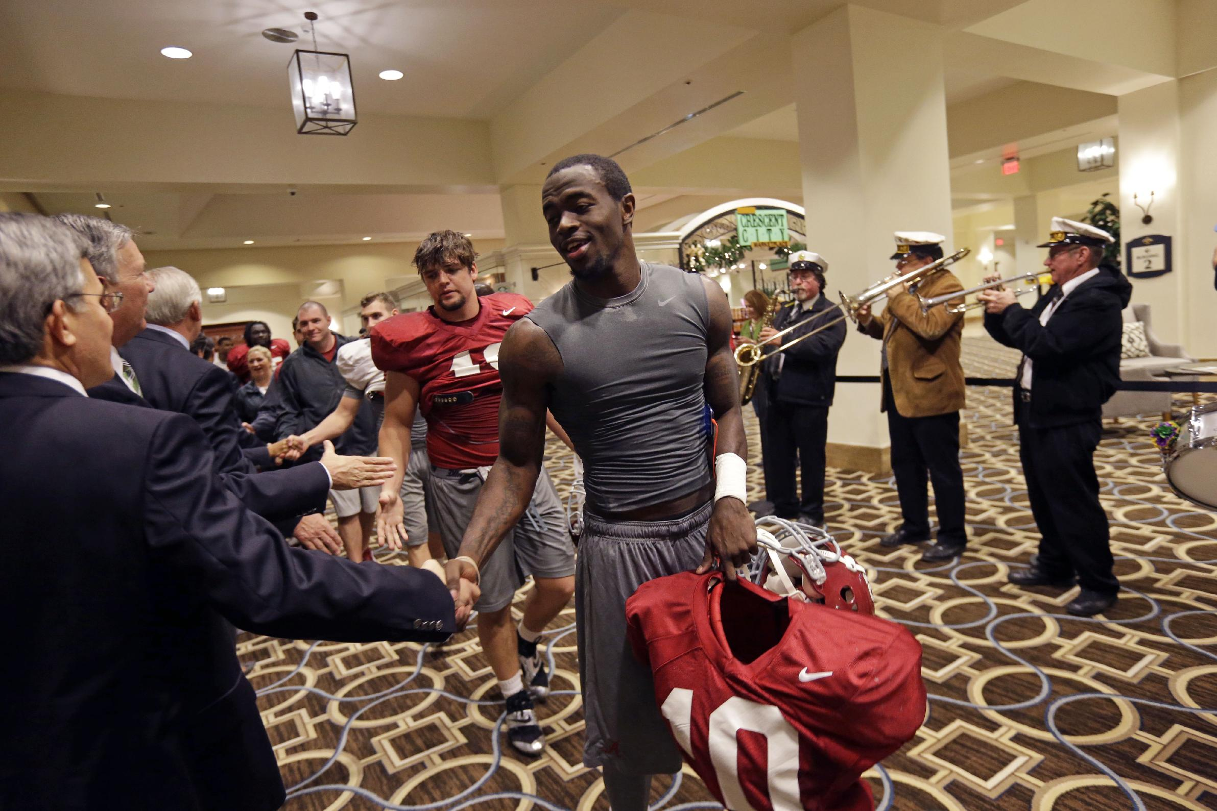 Alabama tight end Issac Leon is greeted by Sugar Bowl Committee members as Alabama players arrive after practice in New Orleans, Friday, Dec. 27, 2013. Alabama will play Oklahoma in the Sugar Bowl on Jan. 2