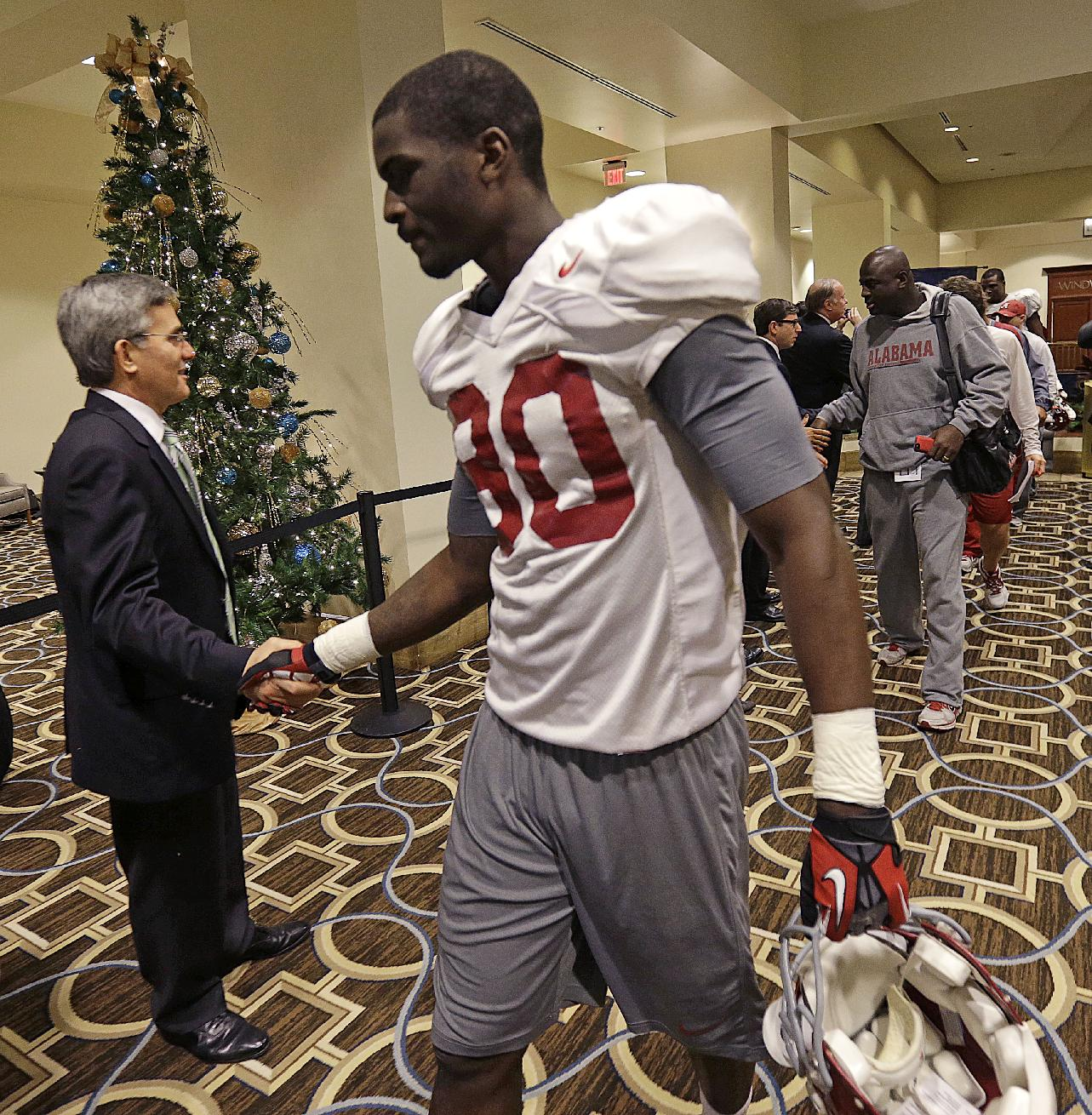 Alabama wide receiver Raheem Falcon (80) is greeted by Sugar Bowl Committee members Alabama players arrive at their hotel after their first team practice in New Orleans, Friday, Dec. 27, 2013. Alabama will play Oklahoma in the Sugar Bowl NCAA college football game on Jan. 2