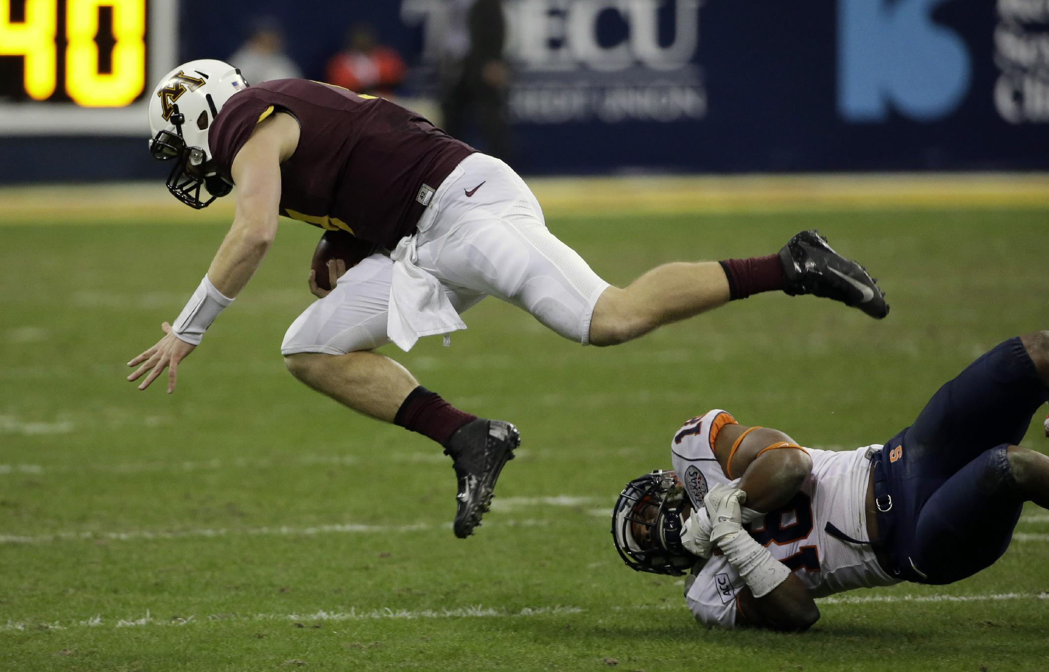 Minnesota quarterback Philip Nelson, left, is tripped by Syracuse defensive back Darius Kelly (18) during the third quarter of the Texas Bowl NCAA college football game on Friday, Dec. 27, 2013, in Houston. Syracuse won 21-17